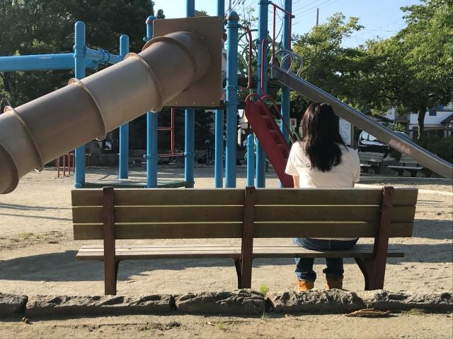 公園の絵ベンチに一人で座るママ