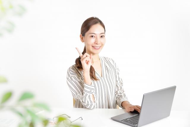 パソコン作業をしながら指差しする女性