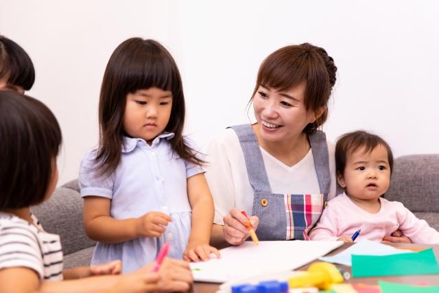 様々な年齢の子供と遊ぶ保育士